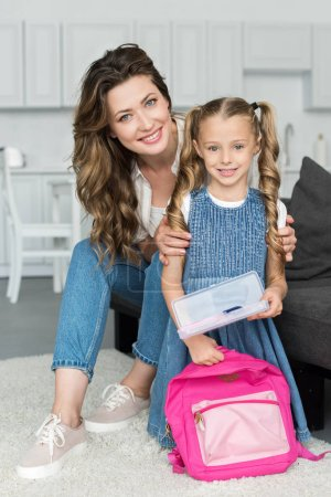 smiling mother and little daughter with school supplies and backpack at home, back to school concept