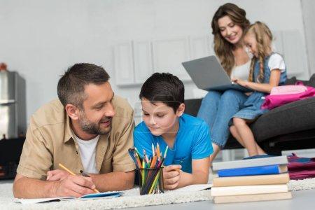 Photo pour Mise au point sélective de l'homme, aider les fils avec les devoirs alors que la mère et la fille avec portable sur canapé ensemble à la maison - image libre de droit
