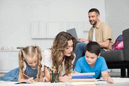 Photo pour Foyer sélectif de la mère aidant les enfants avec des devoirs tout en homme utilisant un ordinateur portable sur le canapé à la maison - image libre de droit