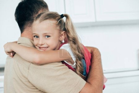 father and smiling daughter with backpack hugging each other in kitchen at home, back to school concept