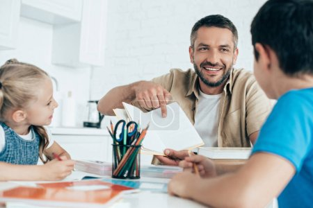 smiling father and kids doing homework together at home