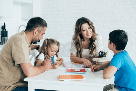 parents helping children with homework at table at home