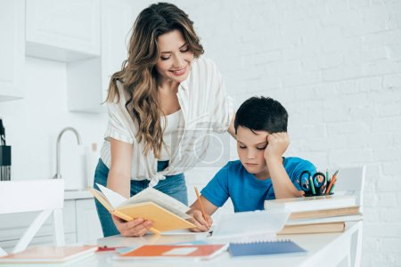 portrait of mother helping bored son with homework in kitchen at home
