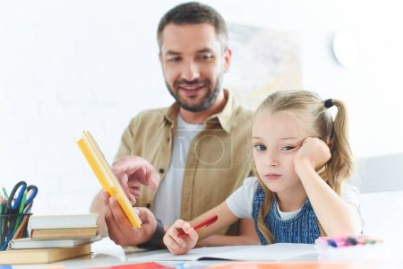father and bored daughter doing homework together at home