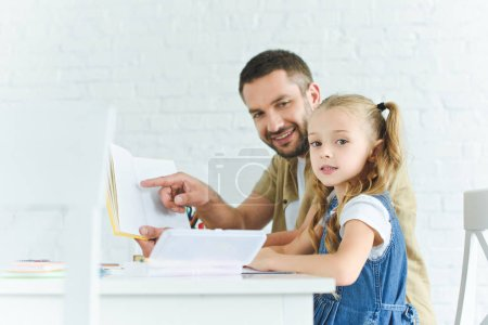 side view of smiling father and little daughter doing homework together at home
