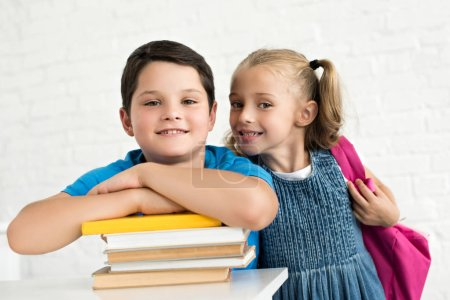 portrait of smiling boy at table with books and little sister with backpack near by at home