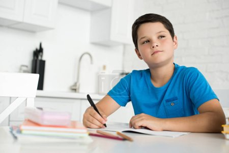 portrait of pensive boy doing homework alone at table at home
