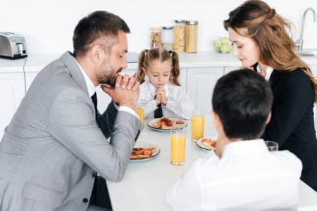 family praying at table during breakfast in kitchen at home