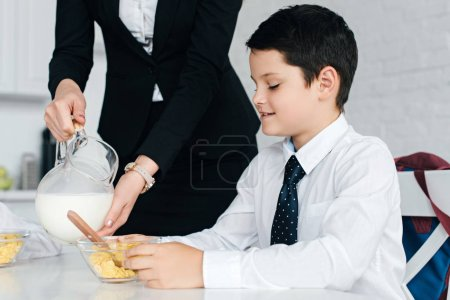 partial view of woman in suit pouring milk into sons bowl with breakfast at home