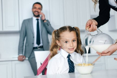 selective focus of kid in school uniform at table with breakfast and mother pouring milk into bowl with crunches at home, back to school concept