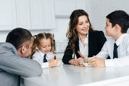family in suits and school uniform having breakfast in kitchen together