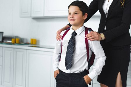Photo for Partial view of mother in suit and son in school uniform with backpack in kitchen at home, back to school concept - Royalty Free Image