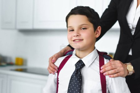partial view of mother in suit and son in school uniform with backpack in kitchen at home, back to school concept