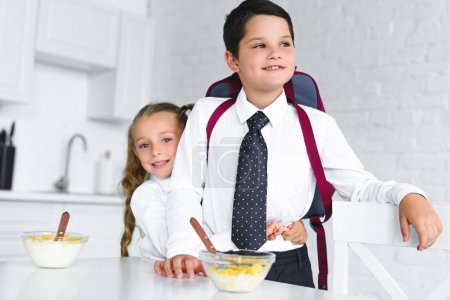 little sister hugging brother in school uniform with backpack at table with breakfast in kitchen at home, back to school concept