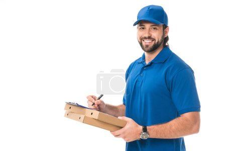 happy delivery man holding boxes with pizza writing on clipboard isolated on white