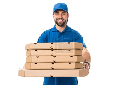 handsome happy delivery man holding boxes with pizza and smiling at camera isolated on white