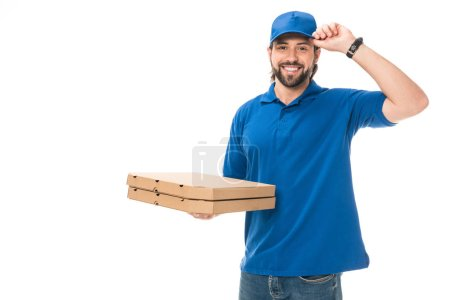 happy delivery man holding boxes with pizza adjusting cap, smiling at camera isolated on white