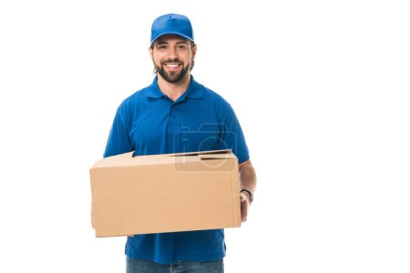handsome happy young delivery man holding cardboard box and smiling at camera isolated on white
