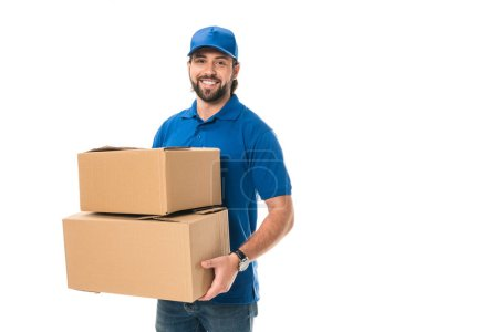 Photo for Handsome happy young delivery man holding cardboard boxes and smiling at camera isolated on white - Royalty Free Image