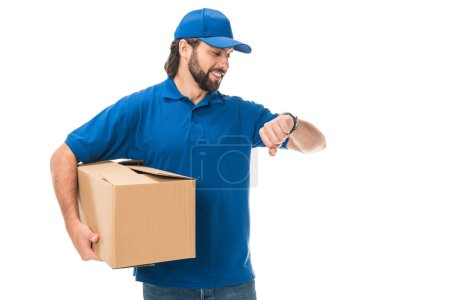smiling delivery man holding cardboard box and checking wristwatch isolated on white