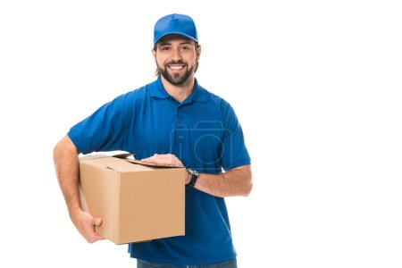 handsome young delivery man holding cardboard box and smiling at camera isolated on white