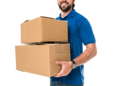 cropped shot of smiling delivery man holding cardboard boxes isolated on white