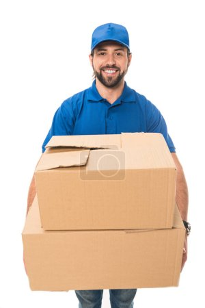 handsome happy young delivery man holding cardboard boxes and smiling at camera isolated on white
