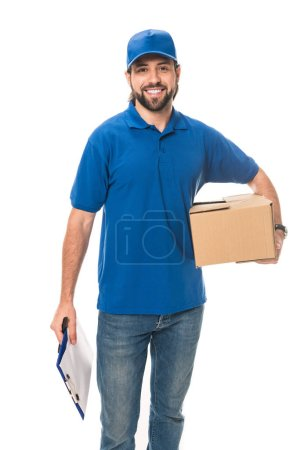 smiling young delivery man holding cardboard box and blank clipboard isolated on white