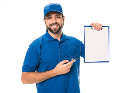 handsome young delivery man pointing at blank clipboard and smiling at camera isolated on white