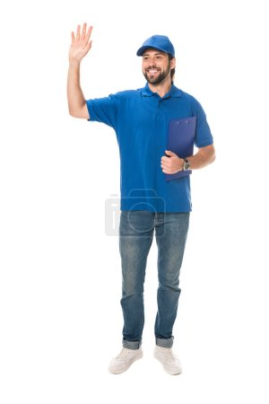 full length view of happy young delivery man holding clipboard and waving hand isolated on white
