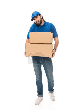young delivery man holding cardboard boxes and talking by smartphone isolated on white