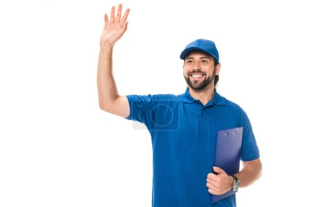 happy young delivery man holding clipboard and waving hand isolated on white