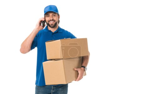 Photo for Happy young delivery man holding boxes, talking by smartphone and smiling at camera isolated on white - Royalty Free Image