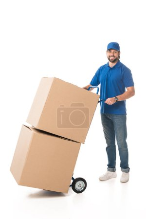 handsome young delivery man carrying boxes and smiling at camera isolated on white