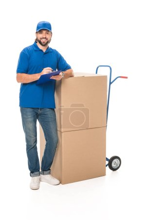 Photo for Handsome young delivery man writing on clipboard, leaning at boxes and smiling at camera isolated on white - Royalty Free Image