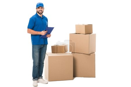 full length view of handsome young delivery worker holding clipboard and smiling at camera while standing near boxes isolated on white