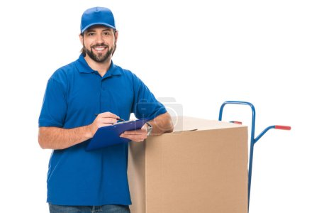 happy young delivery man writing on clipboard and smiling at camera isolated on white