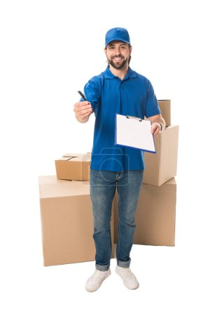 happy young delivery man holding clipboard and smiling at camera isolated on white