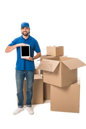 Photo for Young delivery man holding digital tablet with blank screen and smiling at camera while standing near boxes isolated on white - Royalty Free Image