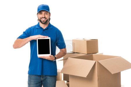 handsome delivery man holding digital tablet with blank screen and smiling at camera isolated on white