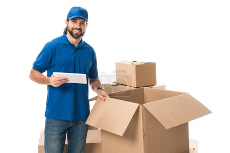 young delivery man using digital tablet and smiling at camera isolated on white