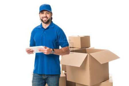 handsome delivery man using digital tablet and smiling at camera isolated on white