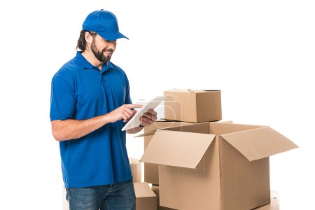 smiling delivery man using digital tablet while standing near boxes isolated on white