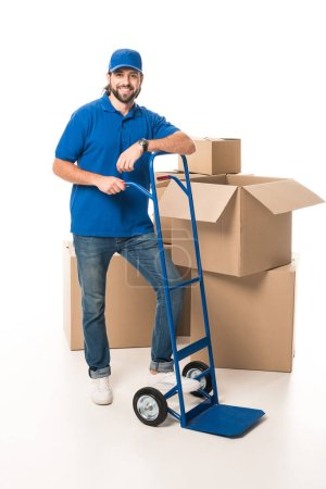 full length view of handsome happy delivery man smiling at camera isolated on white