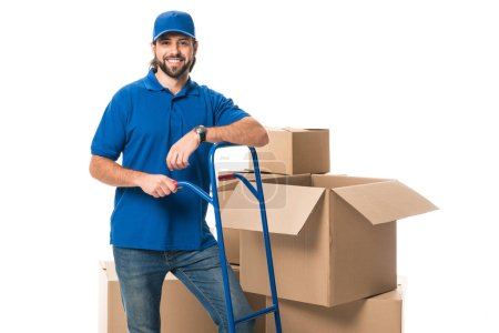 handsome happy delivery man standing near cardboard boxes and smiling at camera isolated on white