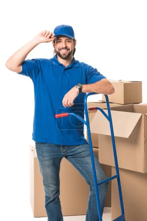 handsome delivery man standing near cardboard boxes and smiling at camera isolated on white