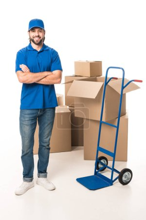 confident delivery man standing with crossed arms and smiling at camera isolated on white