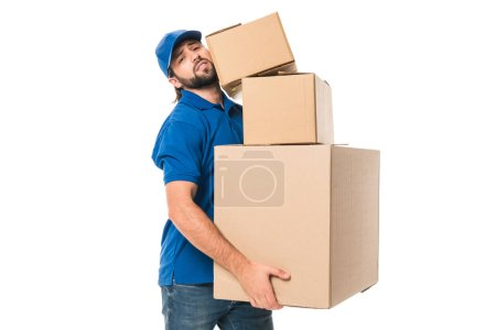 tired delivery man holding stacked cardboard boxes and looking at camera isolated on white