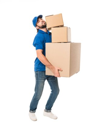 full length view of tired delivery man holding stacked cardboard boxes and looking at camera isolated on white