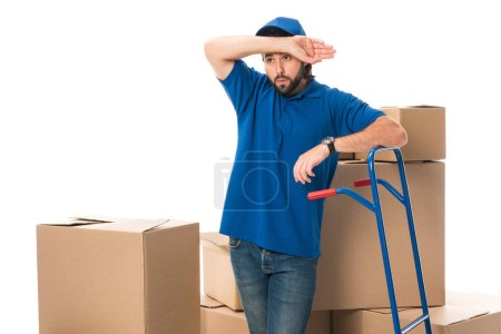 tired delivery man standing between cardboard boxes and looking away isolated on white